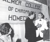 HT Hughes (rt) presenting college president, Dave Palmer (lft), a gold Chiropractic Diamond Jubilee Commemorative Medal at the 1969 Palmer Homecoming. (Agnes Palmer - extreme left)